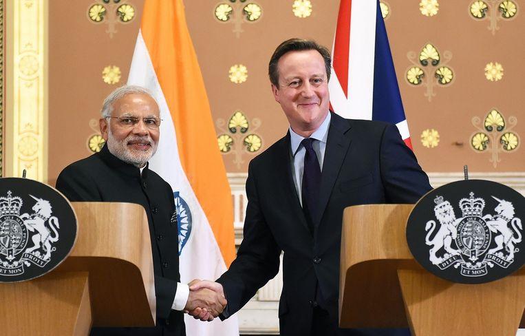 Narendra Modi en David Cameron schudden elkaar de hand. Beeld null