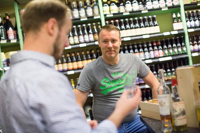 Sander Pardijs in zijn slijterij in Vorden terwijl hij de fijne kneepjes van het proeven van whisky uitlegt.