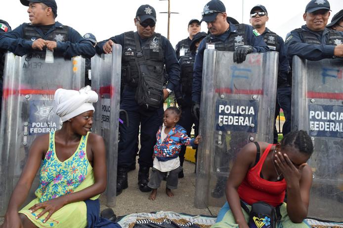 Een meisje loopt tussen agenten bij een detentiecentrum op de grens met Mexico.