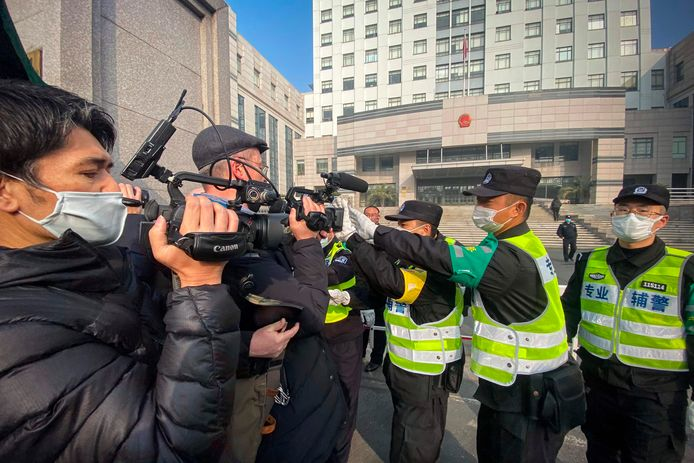 Agenten houden journalisten tegen buiten Shanghai Pudong New District People's Court, waar de burgerjouraliste maandag werd veroordeeld.