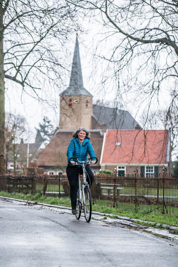 Annemiek Hellings op de fioets in de buurt van de Ellecomse dorpskerk.