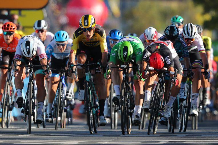 Caleb Ewan (rode helm) drukt zijn fiets nét iets eerder over de finish dan Peter Sagan (links) en Sam Bennett (in het groen). Beeld AFP