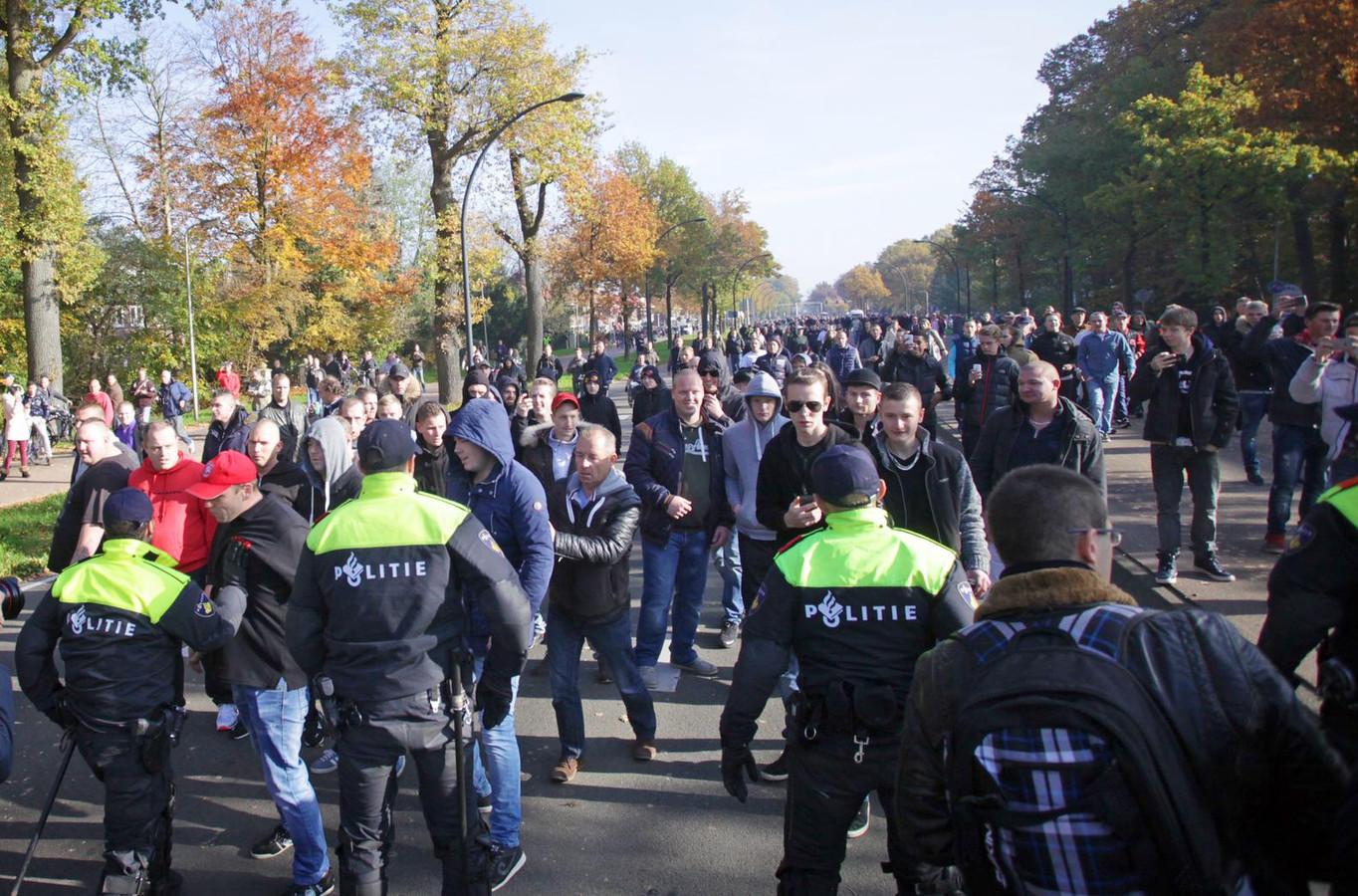 Deelnemers aan een betoging tegen de komst van een asielzoekerscentrum staan tegenover de politie. De burgemeester van Enschede gaf opdracht de betoging te stoppen