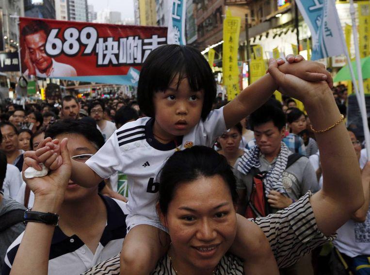 Een demonstrant met haar kind op haar nek. Achter haar is een spandoek te zien waarop staat 'Ga snel weg', met een foto van de premier van Hongkong. Beeld reuters