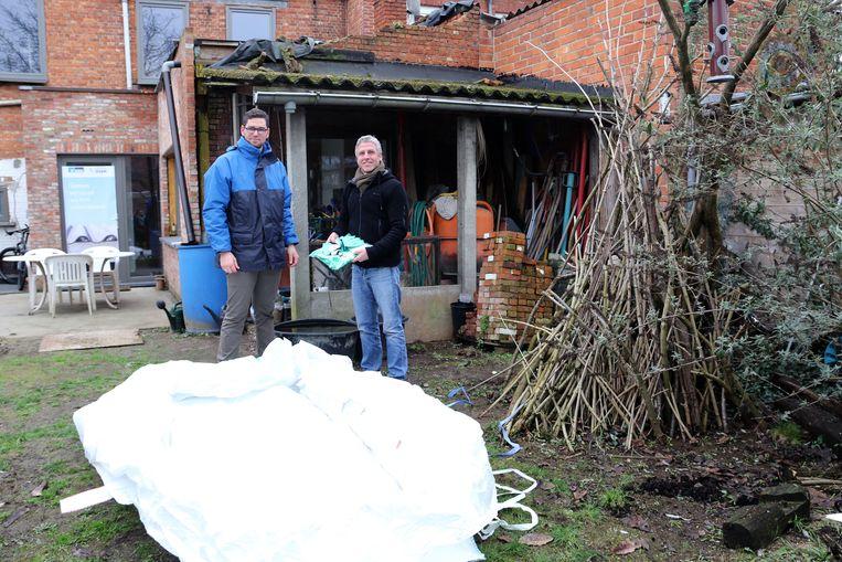 IOK- medewerker Stijn Ruymaekers en bewoner Jiri Van Peer met een plaatzak. Op de achtergrond zie je enkele asbesthoudende golfplaten.
