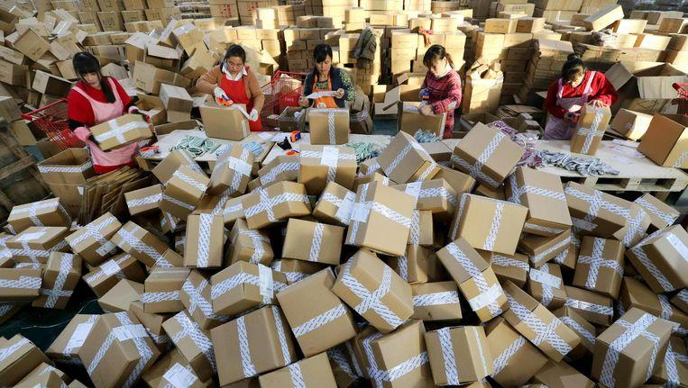 Chinese werknemers van webshop Alibaba sorteren pakketjes voor verzending Beeld afp