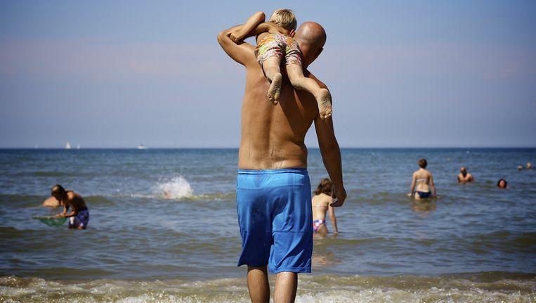Een vader loopt met zijn zoon naar de zee op een van de warmste dagen van het jaar. Beeld anp