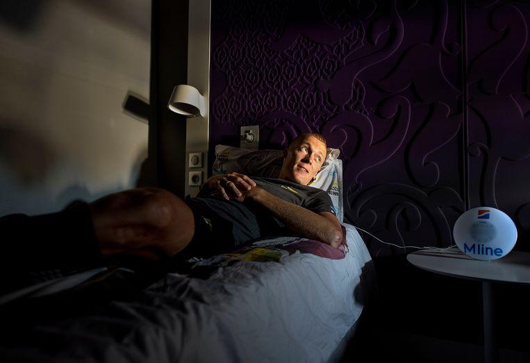 Robert Gesink slaapt op een aangepast bed in zijn hotelkamer, met naast hem een wekker met langzaam sterker wordend licht. Beeld Klaas Jan van der Weij / de Volkskrant