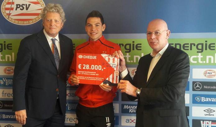 Hirving Lozano en Toon Gerbrands reiken bij PSV de opbrengst van PSV-Pachuca uit aan voorzitter Peter van den Berg van het Rode Kruis Eindhoven en omgeving.