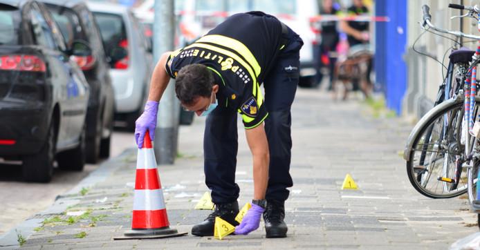 Een politieman merkeert de plaats waar de kogelhulzen liggen.