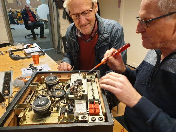 Piet Wevers repareert een cd-speler voor een bezoeker.