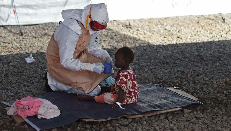 Een ebola-patiënt en een verpleegkundige in Sierra Leone. Beeld afp