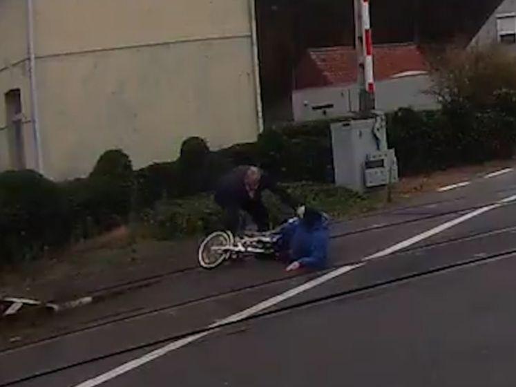 Bejaarde vrouw valt met fiets aan overweg, buschauffeur snelt net op tijd te hulp