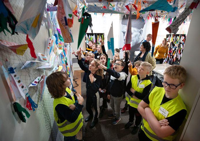 Leerlingen uit Zeilberg wijzen naar hun creaties onder toeziend oog van de bewakers.