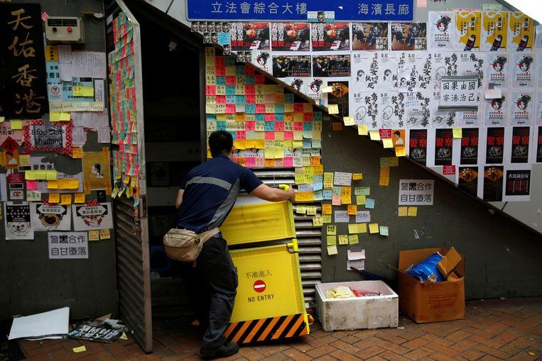 Een man bergt iets op in een ruimte onder een voetgangersbrug. Op het hokje zijn kleine post-its geplakt met commentaar.  Beeld REUTERS