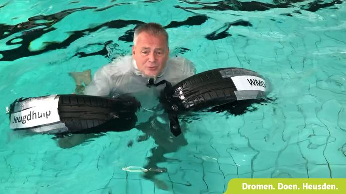 Wethouder Peter van Steen van de gemeente Heuden in het water van zwembad Die Heygrave in Vlijmen, als ludieke oproep voor meer steun vanuit het Rijk voor de alsmaar stijgende kosten van jeugdzorg en Wmo.