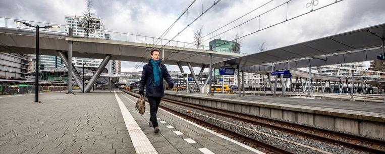 Ombudsman Bram Hansma met achter hem de brug waarmee voetgangers en fietsen alle sporen van Utrecht CS kunnen oversteken. Er zijn evenwel geen trappen van en naar de perrons. Hansma: 'Dan investeer je miljarden in treinen die drie minuten eerder arriveren, maar laat je reizigers tien minuten omlopen. Die moeten door de stationshal.' Beeld Raymond Rutting / de Volkskrant