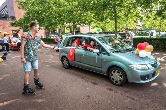 TILBURG, Pix4Profs-Ron Magielse bij de Rooi Pannen is een drive-inn opgezet op de parkeerplaats voor de diplomauitreiking. geslaagde Fleur Grielis krijgt alvast een drankje aangereikt op 1,5 meter afstand, nadat de auto eerst door de carwash is geweest.