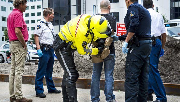 Politieagenten arresteerden de verdachte gisteren. De zakken om zijn handen zijn vermoedelijk om sporen veilig te stellen.