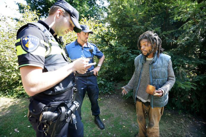 De politie praat met een dakloze in het Valkenbergpark in Breda.