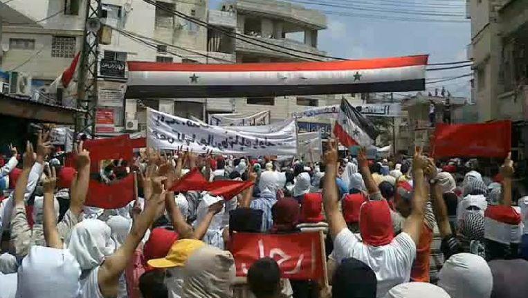 Een demonstratie in de Syrische stad Latakia. Mensen bedekken hun gezicht zodat ze niet herkend worden. Beeld epa