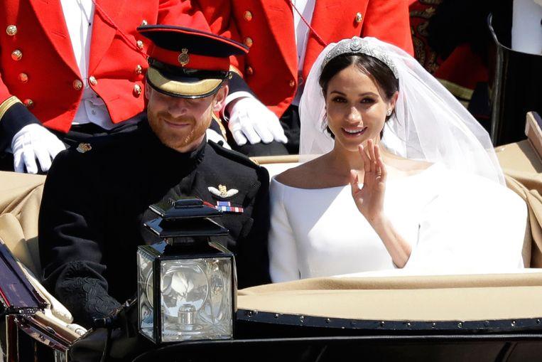 Meghan Markle en prins Harry maken een rit in een koets na hun huwelijksceremonie. Beeld AP
