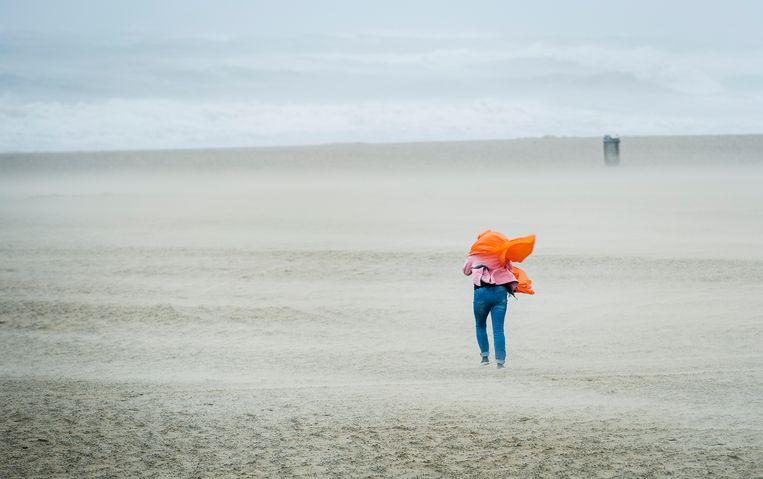Een wandelaar trotseert het strand van Scheveningen tijdens een officiële zomerstorm in 2015. Beeld ANP