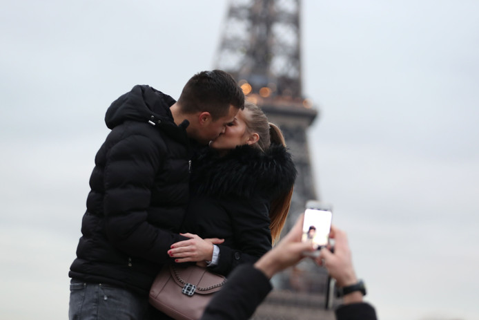 Twee toeristen geven elkaar een kus in Parijs.
