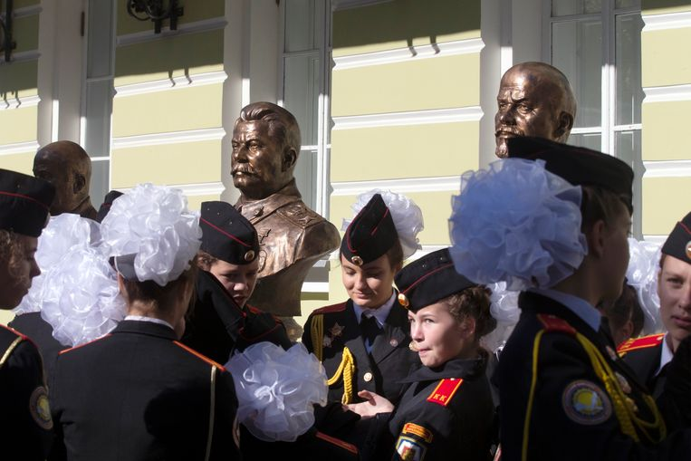 Leerlingen bij de onthulling van Stalins buste om de 'Straat van de heersers' in Moskou. Stalin staat er naast Lenin. Beeld AP