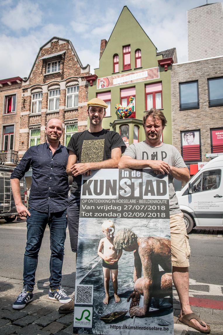 Kevin Soenens, David Maertens en Jurgen Lievens. Tussen hen zie je het gebouw op de achtergrond, met de kip.