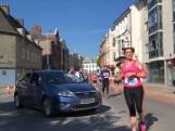 Vrouw rijdt met auto parcours op tijdens halve marathon