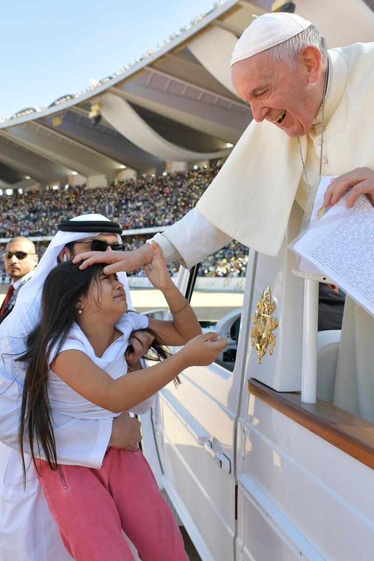De paus zegent een meisje bij aankomst in het Zayed Sports City Stadion. Beeld AFP