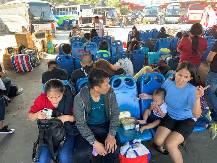 Gestrande reizigers wachten aan de bushalte in Manila.