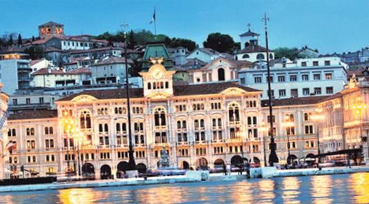 Het stadhuis van Trieste bij avond, op De haven van Grado, dat net als Venetië in een lagune ligt. de Piazza Unità dell'Italia.