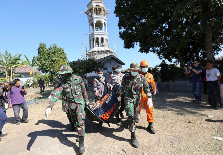 Reddingswerkers dragen het lichaam van een slachtoffer van de aardbeving in het noorden van Lombok. Beeld AP
