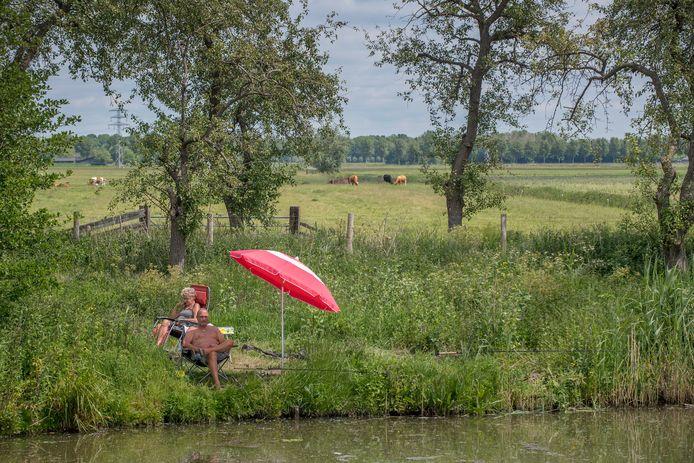 Petra en Erik Bockmeulen uit Vianen genieten langs de waterkant van het mooie weer. Erik vist op brasem en Voorntjes en Petra leest op haar e-book een roman van Nora Roberts.