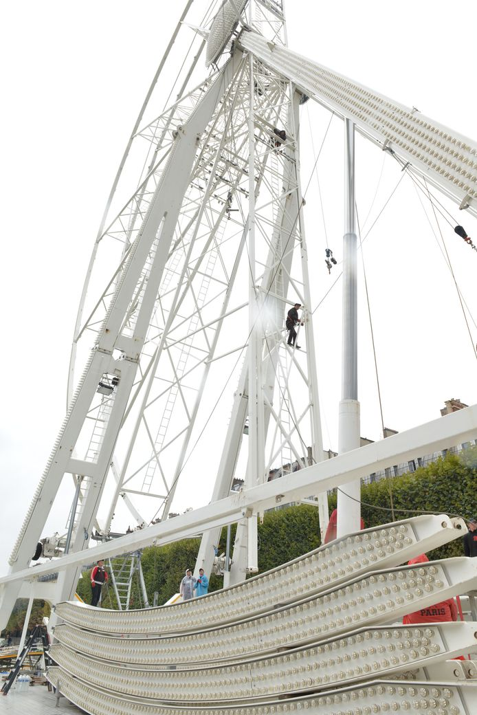 Gezekerd met veiligheidskabels zijn enkele arbeiders bezig met het uit elkaar halen van het rad in Parijs.