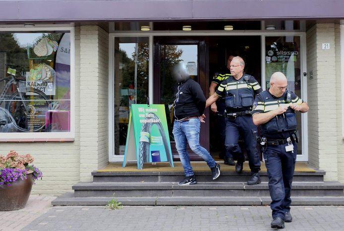 De verdachte wordt door de politie meegenomen
