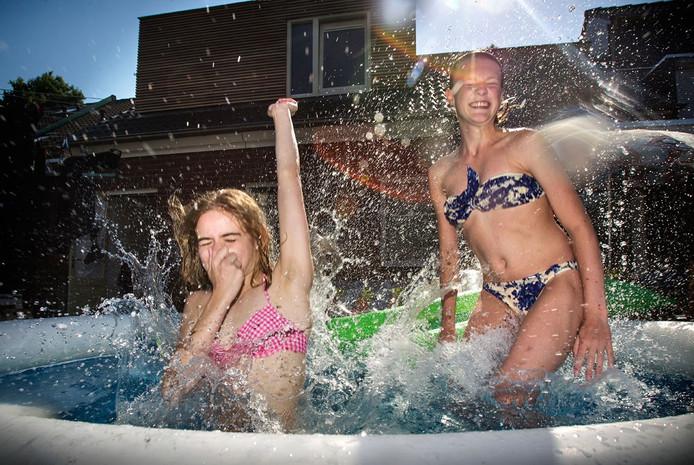 Yente (l) en Nina (r) zoeken verkoeling in het zwembad in een Deurnese achtertuin.