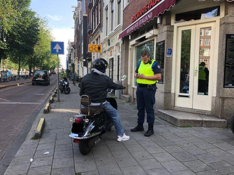 Ambtenaar Jasper van Eijk beboet een snorfietser die over het fietspad rijdt. Beeld Barbara Vollebregt