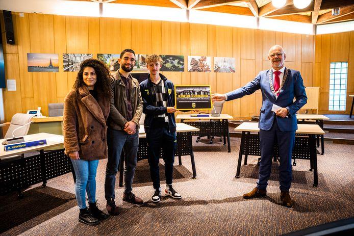 Burgemeester van Rheden Carol van Eert (rechts) geeft een seizoenkaart aan Incluzio-jongerenwerkers Rachel Hanna en Mohamed Bouraarassi en Marouan Berradame (van links naar rechts).