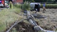Wagen knalt elektriciteitspaal middendoor en belandt op zijkant in weide: brandweer bevrijdt koppel zestigers uit wrak