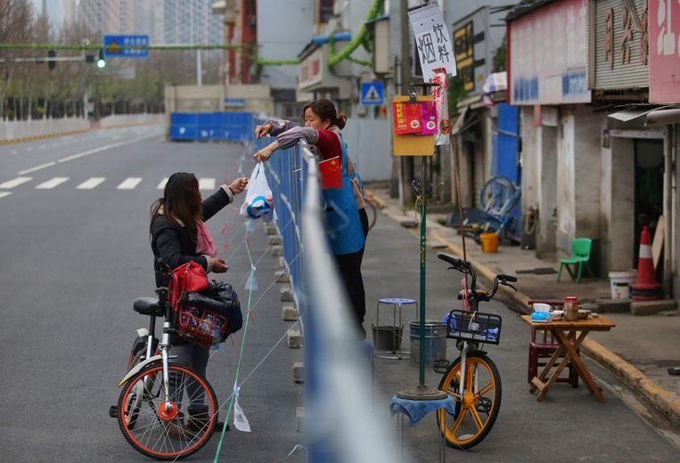Meeschrijven aan de geschiedenis van het coronavirus kan net zo eenvoudig zijn als boodschappen brengen naar een afgesloten buurt, zoals hier in Wuhan. Beeld AFP