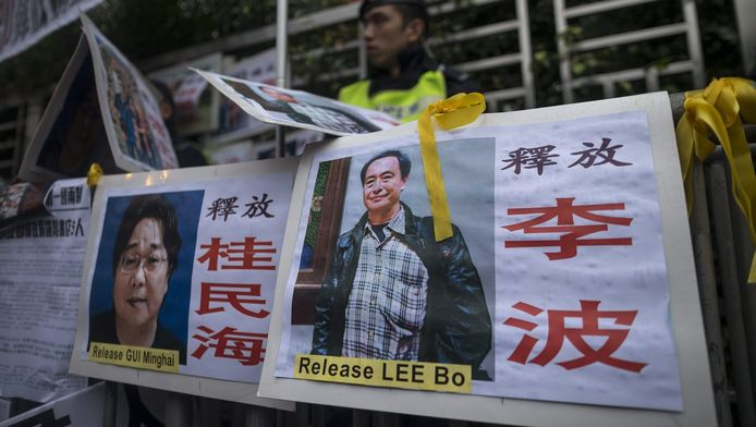 Demonstranten lopen met spandoeken van de verdwenen medewerkers van een boekhandel. Links Gui Minhai.
