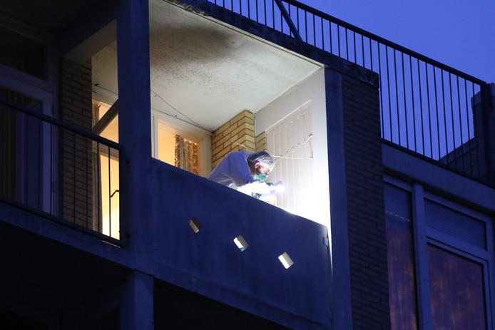 Een rechercheur onderzoekt  het balkon van de woning waar de 85-jarige vrouw dood werd gevonden.