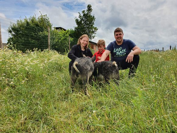 Alexander en Anneleen met een van de kinderen in een weide met loslopende varkens. Dat is The Art of Nature in Merksplas.