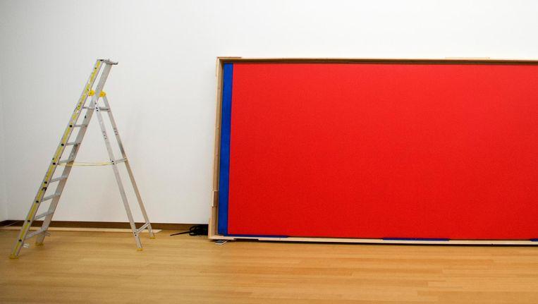 Een beveiliger bij het schilderij Who is afraid of Red, Yellow and Blue van Barnett Newman dat in 2014 wordt opgehangen in het Stedelijk Museum. Beeld anp