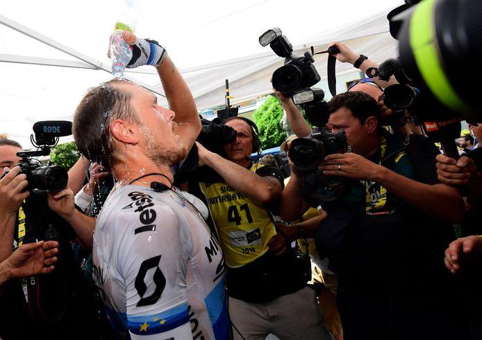 Ritwinnaar Matteo Trentin besprenkelt zich met een flesje water.