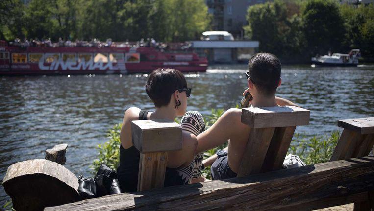 Twee mensen zitten op een bankje langs de rivier Spree in Berlijn Beeld afp