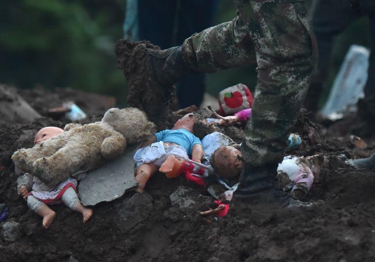Een soldaat loopt langs speelgoed dat in de modder is achtergebleven na de landverschuiving.